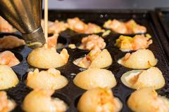 Fermez-vous vers le haut des crevettes roses de cuisson dans la moule avec des trous images libres de droits