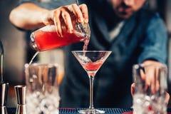 Fermez-vous vers le haut des détails de cocktail cosmopolite de versement de vodka de barman photos stock