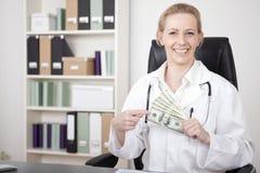 Fermez-vous vers le haut des dollars US heureux de docteur Holding de femme Images libres de droits