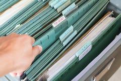 Fermez-vous vers le haut des dossiers dans un meuble d'archivage Photographie stock libre de droits