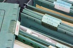 Fermez-vous vers le haut des dossiers dans un meuble d'archivage photographie stock