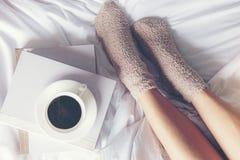 Fermez-vous vers le haut des femmes de jambes sur le lit blanc Le livre de lecture de femmes et le café potable dans le matin dét images stock