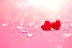 Fermez-vous vers le haut des formes rouges de coeur avec des baisses de l'eau de pluie sur le spon rose Photographie stock libre de droits