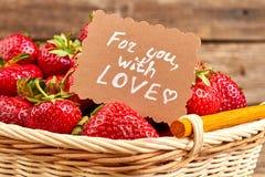 Fermez-vous vers le haut des fraises dans le panier et la note de papier Photographie stock libre de droits