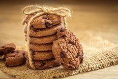 Fermez-vous vers le haut des gâteaux aux pépites de chocolat empilés sur la serviette avec b en bois Photographie stock