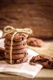 Fermez-vous vers le haut des gâteaux aux pépites de chocolat empilés sur la serviette avec b en bois Photographie stock libre de droits