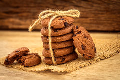 Fermez-vous vers le haut des gâteaux aux pépites de chocolat empilés sur la serviette avec b en bois Image libre de droits