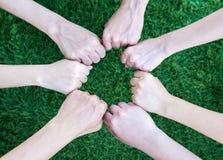 Fermez-vous vers le haut des gens d'affaires asiatiques de mains ensemble au-dessus de l'herbe verte o Image libre de droits