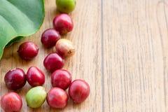 Fermez-vous vers le haut des grains de café frais sur la table en bois Image stock