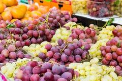 Fermez-vous vers le haut des groupes de raisins verts et pourpres frais à vendre sur l'affichage avec d'autres friuts à un marché Images stock