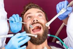 Fermez-vous vers le haut des hommes patients avec la bouche ouverte dans la clinique dentaire images libres de droits