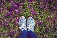 Fermez-vous vers le haut des jambes croisées par femelle marchant sur l'herbe Images stock