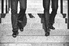 Fermez-vous vers le haut des jambes de l'homme d'affaires deux descendant l'escalier dans la ville moderne photos libres de droits
