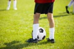 Fermez-vous vers le haut des jambes et des pieds de joueur de football dans les chaussettes blanches et le bl Photos stock