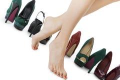Fermez-vous vers le haut des jambes impeccables de femme dans la position rouge brillante de chaussures de talon haut Photo stock