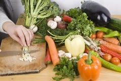 Fermez-vous vers le haut des légumes de découpage de femme dans la cuisine Photographie stock libre de droits