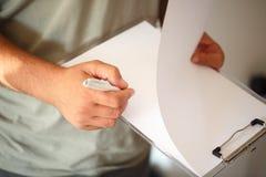 Fermez-vous vers le haut des mains d'homme d'affaires avec l'écriture de stylo sur le papier Photo stock