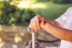 Fermez-vous vers le haut des mains d'homme plus âgé avec son bâton de marche Photo stock