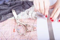 Fermez-vous vers le haut des mains d'un couturier au travail avec le tissu de tissu Images stock