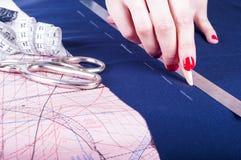 Fermez-vous vers le haut des mains d'un couturier au travail avec le tissu de tissu Mains femelles au travail avec la règle pour  Images stock