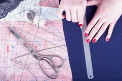 Fermez-vous vers le haut des mains d'un couturier au travail avec le tissu de tissu Mains femelles au travail avec la règle pour  Image stock