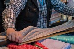 Fermez-vous vers le haut des mains d'un couturier au travail avec le tissu de tissu image libre de droits