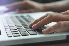 Fermez-vous vers le haut des mains dactylographiant l'ordinateur portable de clavier Image stock