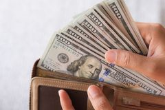 Fermez-vous vers le haut des mains de femme sortant des billets de banque des dollars de l'Amérique d'argent Image libre de droits