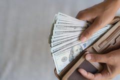 Fermez-vous vers le haut des mains de femme sortant des billets de banque des dollars de l'Amérique d'argent Image stock