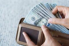 Fermez-vous vers le haut des mains de femme sortant des billets de banque des dollars de l'Amérique d'argent Photo stock