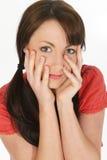 Fermez-vous vers le haut des mains de jeune femme sur le visage Photographie stock libre de droits