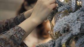 Fermez-vous vers le haut des mains de jouet accrochant de Noël de femme sur l'arbre à l'intérieur clips vidéos