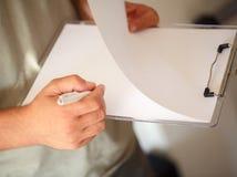 Fermez-vous vers le haut des mains de l'homme avec l'écriture de stylo sur le papier Image stock