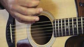 Fermez-vous vers le haut des mains de l'homme jouant le mouvement lent de guitare acoustique banque de vidéos