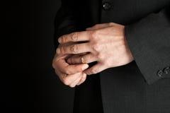 Fermez-vous vers le haut des mains de l'homme retirant la boucle de mariage Photographie stock
