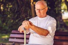 Fermez-vous vers le haut des mains de vieil homme avec son bâton de marche Photo libre de droits