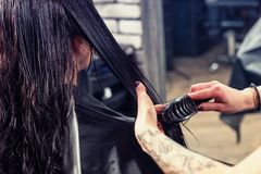 Fermez-vous vers le haut des mains du coiffeur professionnel féminin peignant l'ha humide images libres de droits