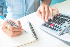 Fermez-vous vers le haut des mains du ` s de femme utilisant la calculatrice et l'écriture sur le carnet, Photos stock