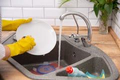 Fermez-vous vers le haut des mains des plats de lavage de femme dans la cuisine images libres de droits