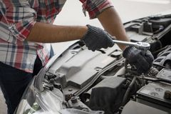 Fermez-vous vers le haut des mains sales d'homme mécanique utilisant l'outil pour fixer la voiture de réparation photos stock