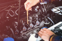 Fermez-vous vers le haut des mains vérifiant le niveau d'huile lubrifiante du moteur de voiture des grandes profondeurs images libres de droits