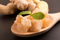 Fermez-vous vers le haut des morceaux cristallisés glacés de sucrerie de gingembre sur la cuillère en bois Photos stock