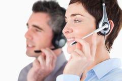 Fermez-vous vers le haut des opérateurs parlant par des écouteurs photo stock
