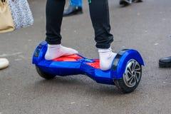 Fermez-vous vers le haut des pieds dans les chaussettes sur le hoverboard photographie stock