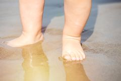 Fermez-vous vers le haut des pieds de bébé jouant avec le sable sur la plage au coucher du soleil Photo stock