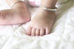 Fermez-vous vers le haut des pieds du ` s de bébé sur le lit de petit morceau Photo libre de droits