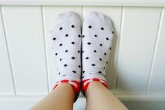 Fermez-vous vers le haut des pieds portant la polka blanche Dot Socks à l'arrière-plan de chambre à coucher Image stock