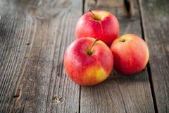 Fermez-vous vers le haut des pommes rouges organiques mûres fraîches avec des baisses de l'eau sur la table en bois rustique L'es Photographie stock