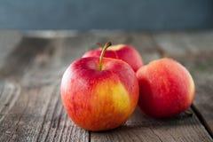 Fermez-vous vers le haut des pommes rouges organiques mûres fraîches avec des baisses de l'eau sur la table en bois rustique L'es Photo libre de droits