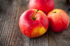 Fermez-vous vers le haut des pommes rouges organiques mûres fraîches avec des baisses de l'eau sur la table en bois rustique L'es Image stock